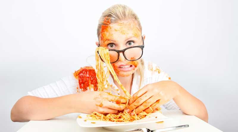 Frau isst Spaghetti mit Fingern