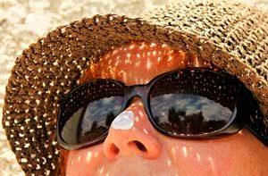 Frau mit Sonnenhut und Sonnencreme
