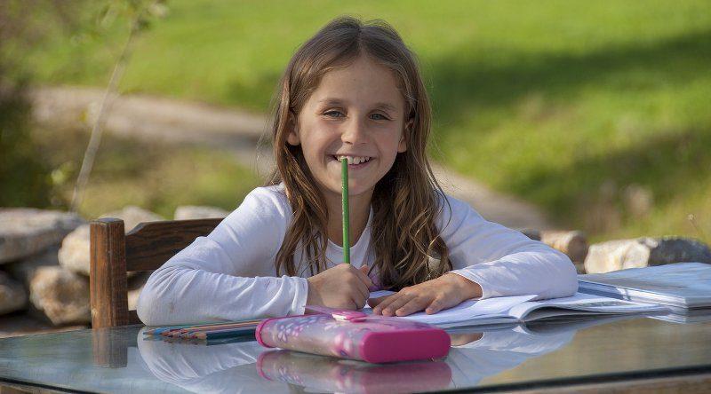 Schulkind sitzt mit Hausaufgaben am Tisch
