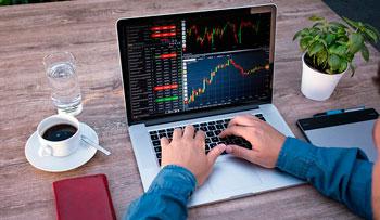 Mann am Laptop beim Forex-Trading