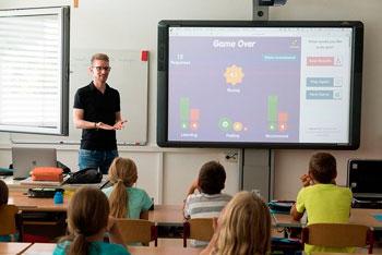Ein Lehrer steht vor einer Klasse am Whiteboard