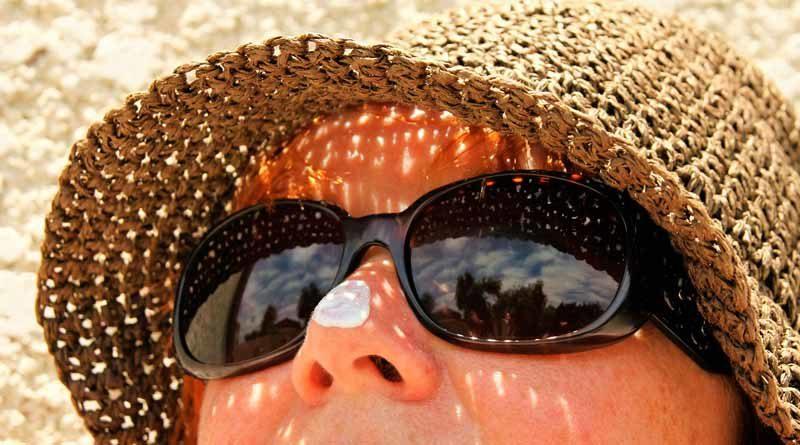 Frau mit Sonnenhut und Sonnecreme