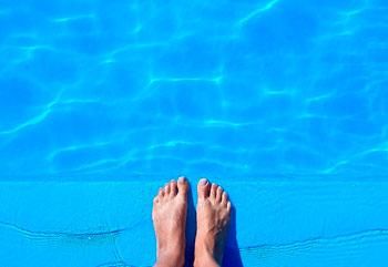 Füße am Rand eines Pools