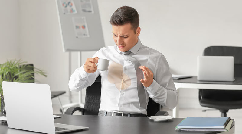Businessmann verschüttet Kaffee auf sein weißes Hemd