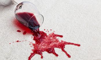 Verschütteter Rotwein auf hellem Teppich
