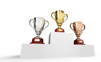 Drei Pokale in gold, silber und bronze auf Podium
