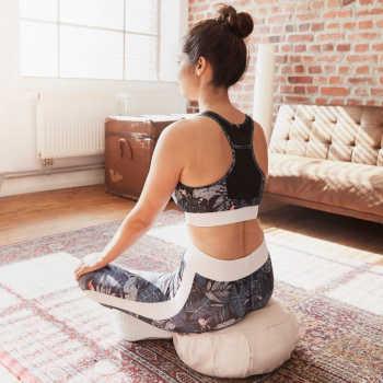 Frau sitzt auf Yogakissen