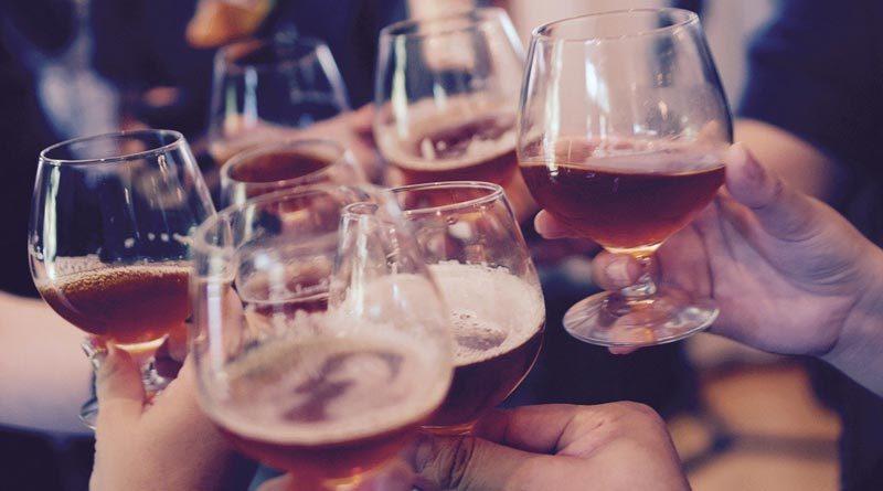 Männer prosten sich mit Bier zu