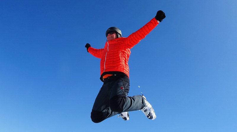 Mann in Schneeanzug springt in die Luft