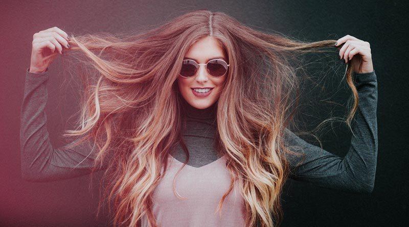 Frau zeigt ihre langen gefärbte Haare