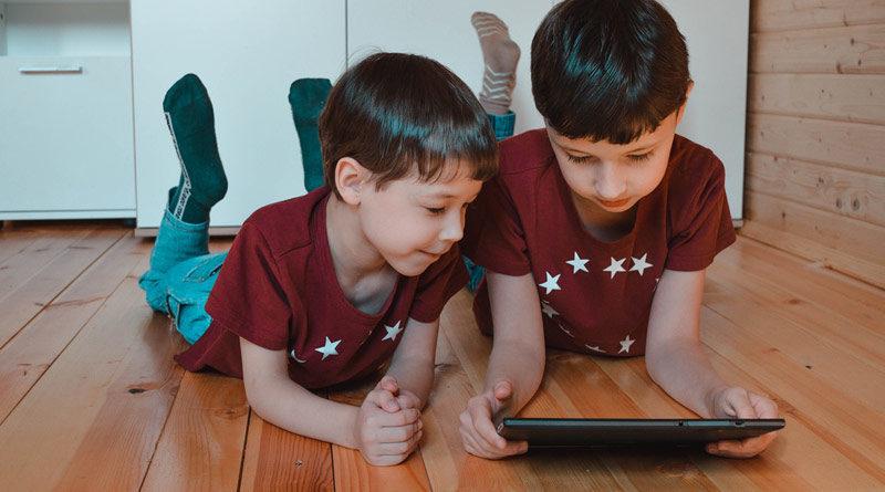 Zwei Brüder liegen auf dem Boden und schauen in ein Tablet